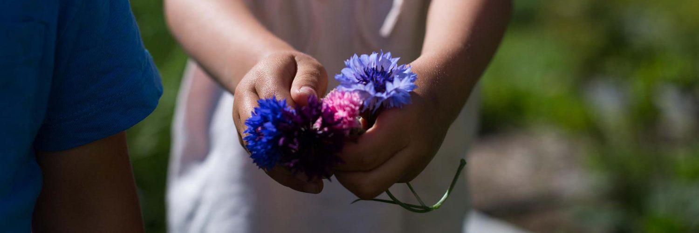 Skogsjö Gård och flicka som håller i blommor